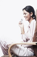 Side profile of a businesswoman sitting on a chair with her legs crossed