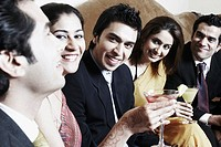 Close-up of three young men and two young women holding martini glasses