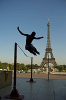 Young man jumping over a balustrade with Inline Skates, Eiffel Tower in the background, back light