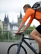 Bicycle courier cycling across bridge, side view