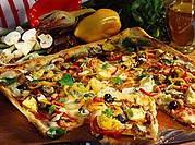 Pizza with colourful topping of peppers, artichokes & olives