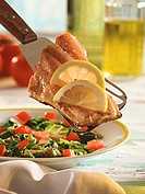 Trout fillet with lemons on server above chard salad