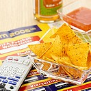 Sports newspaper, tortilla chips and remote control