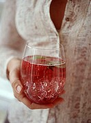 A woman holding a glass of raspberry punch