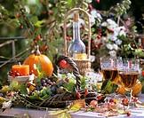 Autumn decoration: basket of vines, leaves, candles, wineglasses