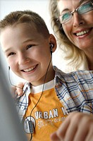 Low angle view of a boy listening to music with his grandmother behind him