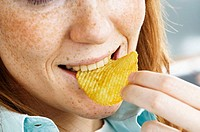 Close-up of a woman biting a potato chips