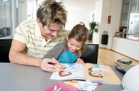 Close-up of a father helping his daughter color