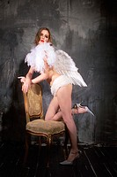 Side profile of a young woman in an angel costume kneeling on a chair