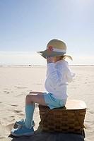 Girl sitting on picnic basket on beach