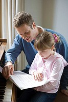 Father and daughter looking at sheet music
