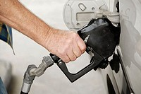 Adult male pumps gas into his car at a gas station