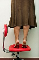A female office worker standing dangerously on an office chair.