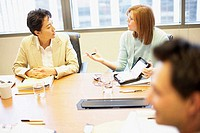 Two businesswomen and a businessman talking in a conference room