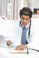 Close-up of a male doctor using a laptop while reading a document