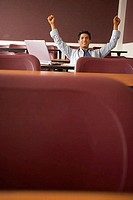 College student sitting in a lecture hall with his arms raised
