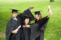 Portrait of two female graduates and a male graduate holding diplomas