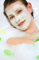 Young woman with face mask taking a bubble bath, close up, portrait