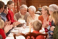 Grandmother with birthday cake and family at dinner table, Richmond, Virginia, United States