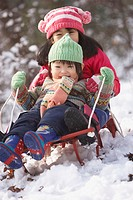 Asian brother and sister on sled