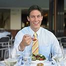 Young man eating at restaurant table, Perth, Australia