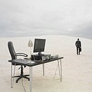 Businessman walking away from desk in the desert, Lancelin, Australia