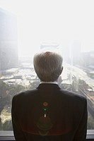 Senior businessman looking out window, Los Angeles, California, United States