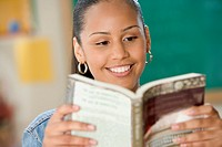 Female Dominican teenager reading a book in classroom