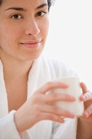 Hispanic woman in a bathrobe holding a mug