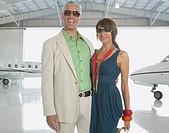 Couple hugging in airplane hanger, Nobato, California, United States