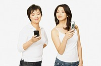 Studio shot of Asian mother and adult daughter with cell phones