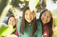 Three young Asian sisters smiling outdoors, San Rafael, California, United States