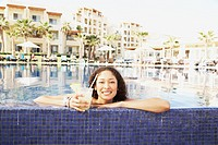 Hispanic woman with drink leaning on pool edge