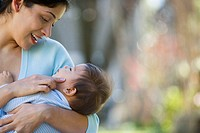 Hispanic mother holding baby and smiling