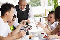 Group of friends having lunch, waiter pouring water at their table