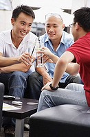 Three guys at a cafe, toasting with drinks