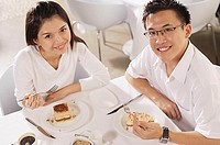 Couple eating dessert in restaurant, looking up at camera