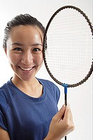 Woman holding badminton racket next to her face, smiling