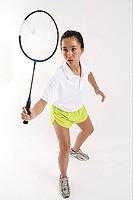 Woman hitting shuttlecock with badminton racket