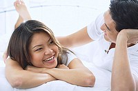 Couple on bed, smiling