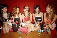 Women sitting side by side, holding drinks