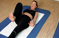 Young woman at the gym, fitness center, doing some gymnastics on a mat, streching