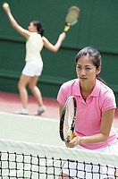 Two women playing tennis, mixed doubles