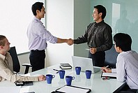 Executives in meeting room, shaking hands