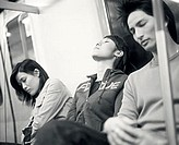 Young adults sleeping on train.