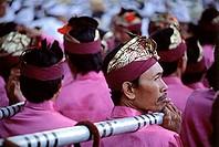 Indonesia, Bali, Besakih Temple, Gamelan players carrying gongs arrive at temple. (grainy)