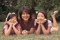 Mother and two daughters lying on grass