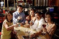 Group of people raising wine glasses, looking at camera