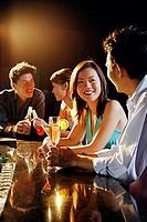 Young adults sitting at bar, talking