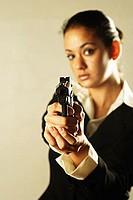 Businesswoman holding gun, looking at camera
